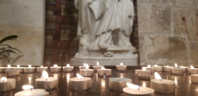 Prayer votives lit under the statue of Anne and Mary.